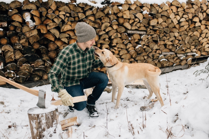 A man takes a break from splitting wood to kiss his yellow lab dog.