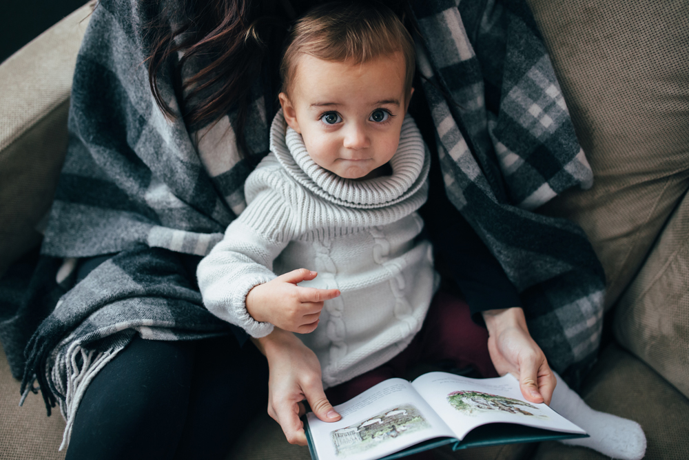 A baby reads a book with mom.