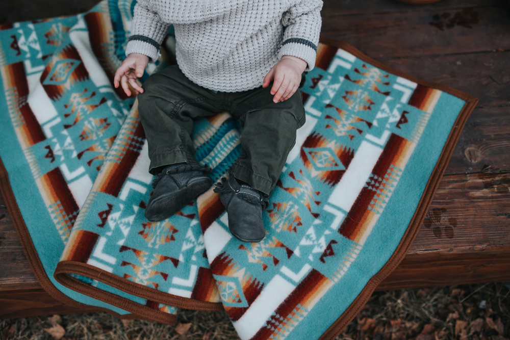 A baby sits on a Pendleton blanket.