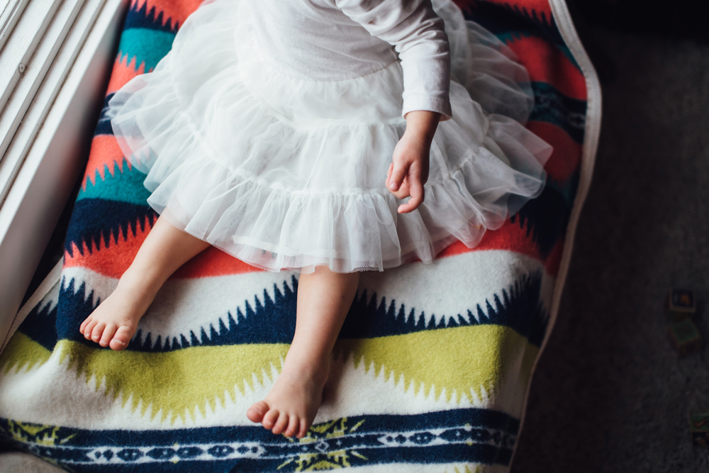 a baby sits on a Pendleton child's blanket.