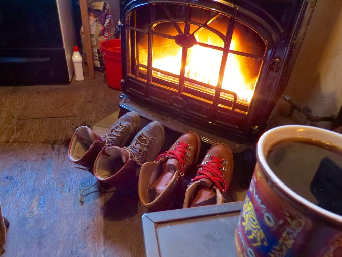 Boots dring by the woodstove with a Pendleton Buffalo Creation coffee mug in the foreground.