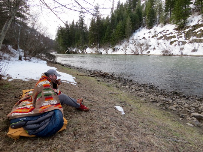 Greg Hatten sits on the banks of the Wallowa River, sipping a warm drink.