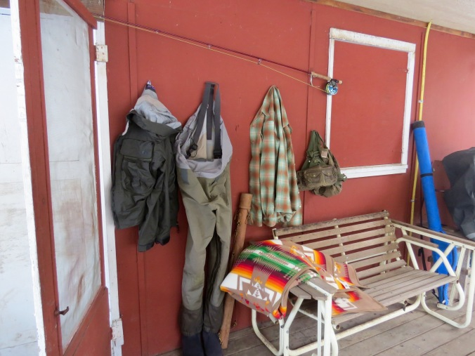 Wadrers, a wool shirt, and a Pendleton blanket on the front porch of a cabin.