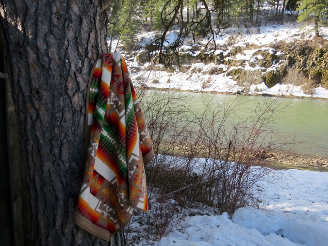 A Chief Joseph blanket hangs on a tree by a riverbank.