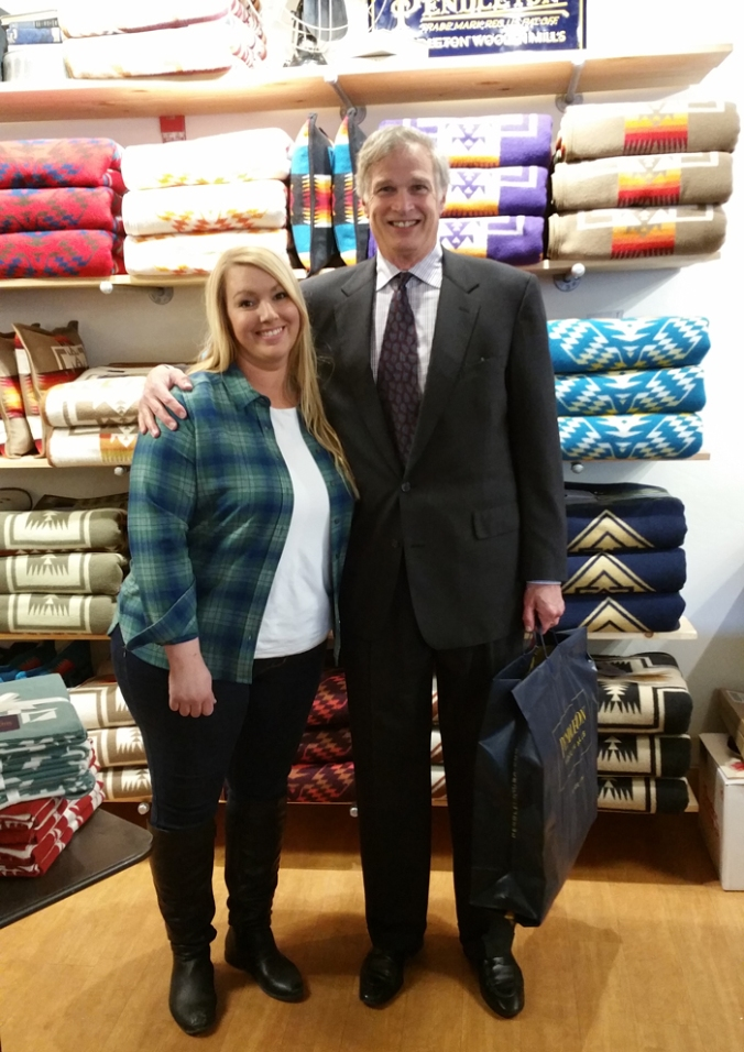 The Eugene Pendleton store's first cutomer poses with a store sales associate in front of the blanket wall.