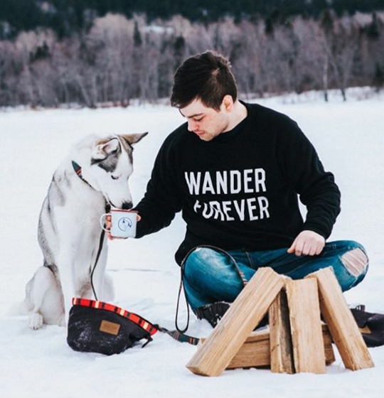 A young man gives his husky a drink from a tin coffee cup.