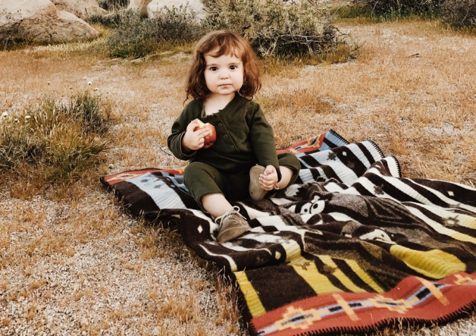 A little girl hoding an apple sits on a Pendleton blanket.