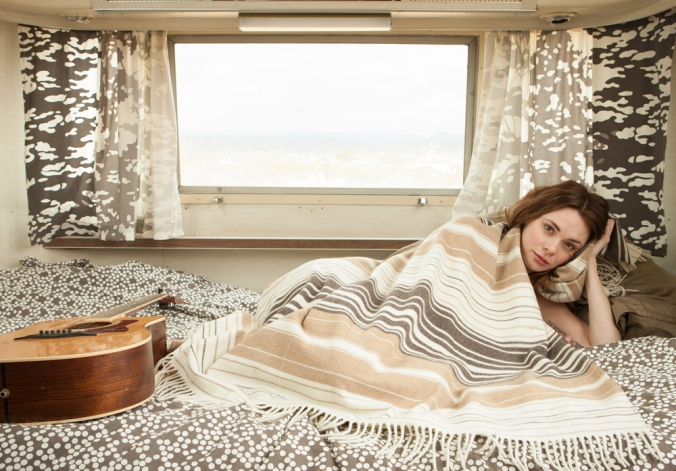 Marina Chavez photo of SuzanneSanto and her guitar, wrapped in a 5th Avenue throw