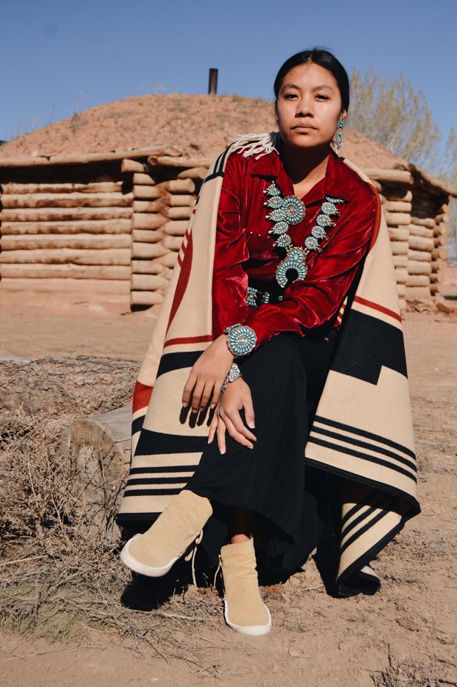 Shondina Lee Yikasbaa poses in traditional Dine clothing, family jewelry, and the Gift of the Earth blanket.