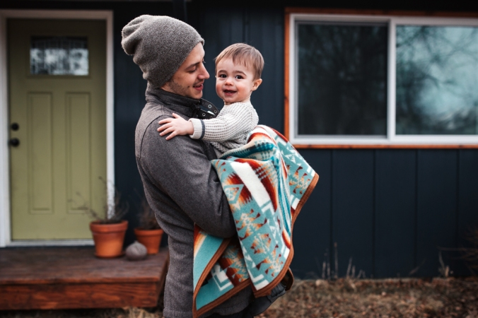 Grace_Adams_ photo of a young man holding a baby in a Pendleton blanket