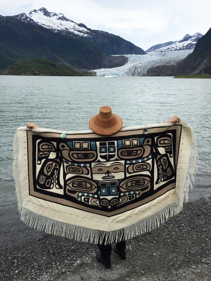 Linda Benson Kusumoto in her traditional Chilkat robe standing in front of the Mendenhall Glacier in Alaska.