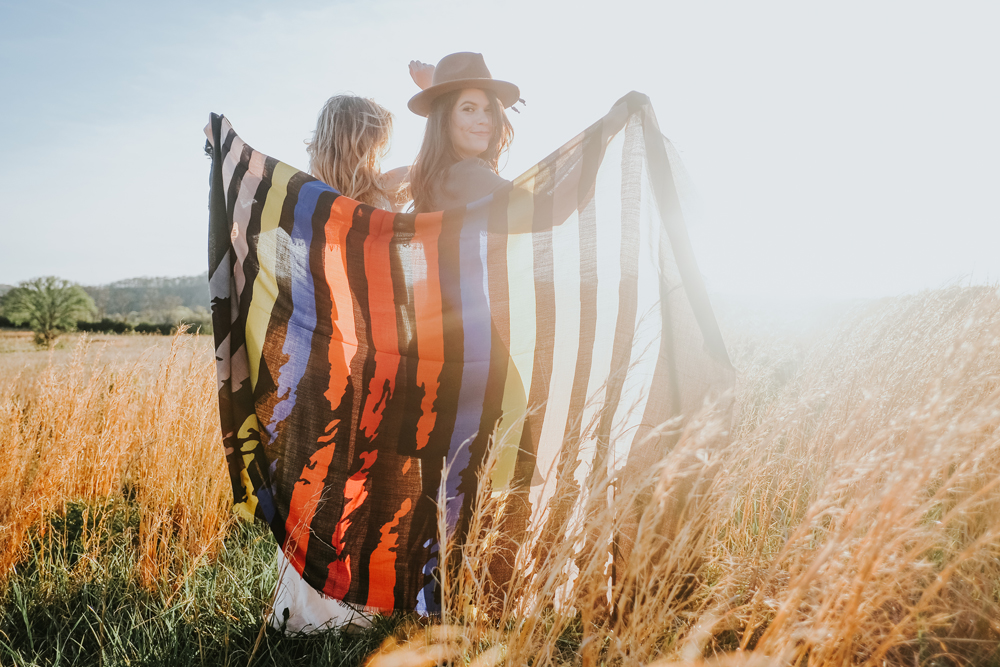 Two women and a scarf in a meadow.