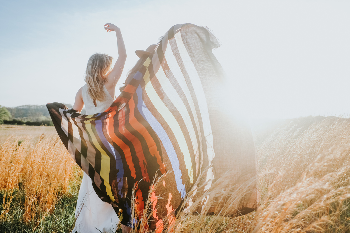 Two women in a meadow raise their arms and a Pendleton scarf to the sun.