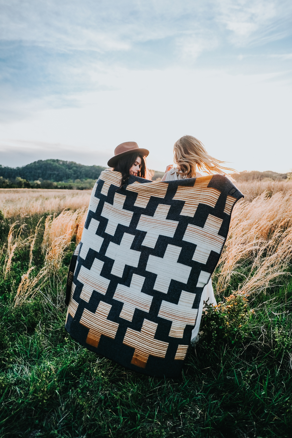 Two women wrap up in a blanket in a meadow.