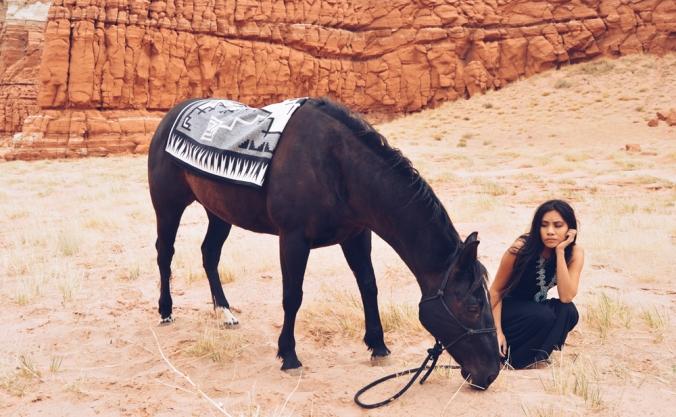 Shondina_Yikasbaa and a horse, horse wearing Pendleton saddle blanket