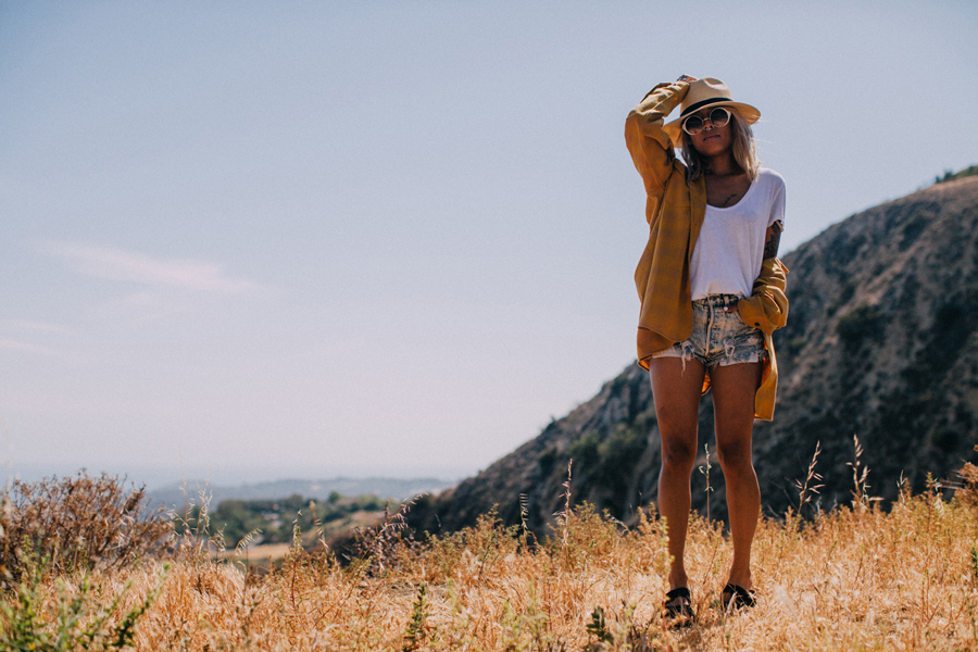 A young woman stands on a hillside, wearing a gold Pendleton shirt and a Pendleton hat.