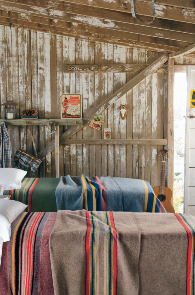 Camp_blankets on beds in a rustic room.