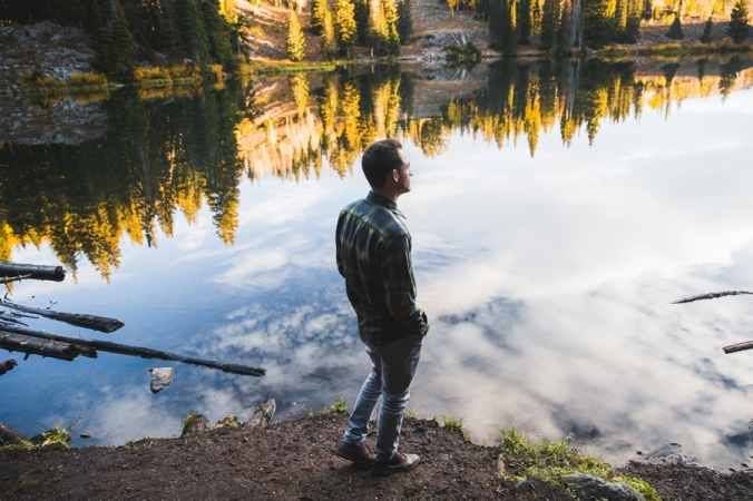 A man stands beside a pond wearing a plaid Pendleton shirt