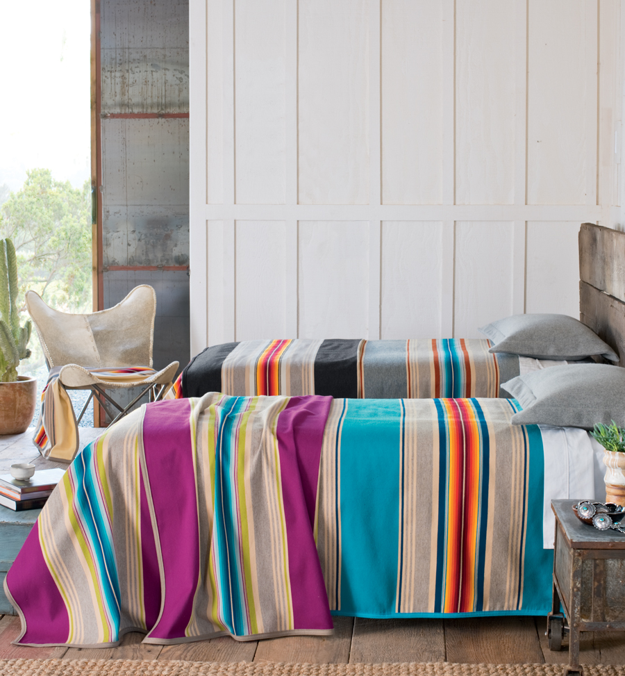 Serape-blankets on beds in a beachy room.
