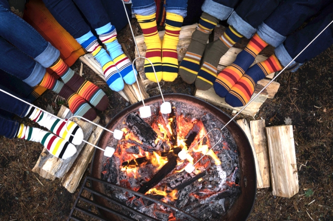 A campfire, over which marshmallows are being toasted, and six people's feet wearing Pendleton socks.