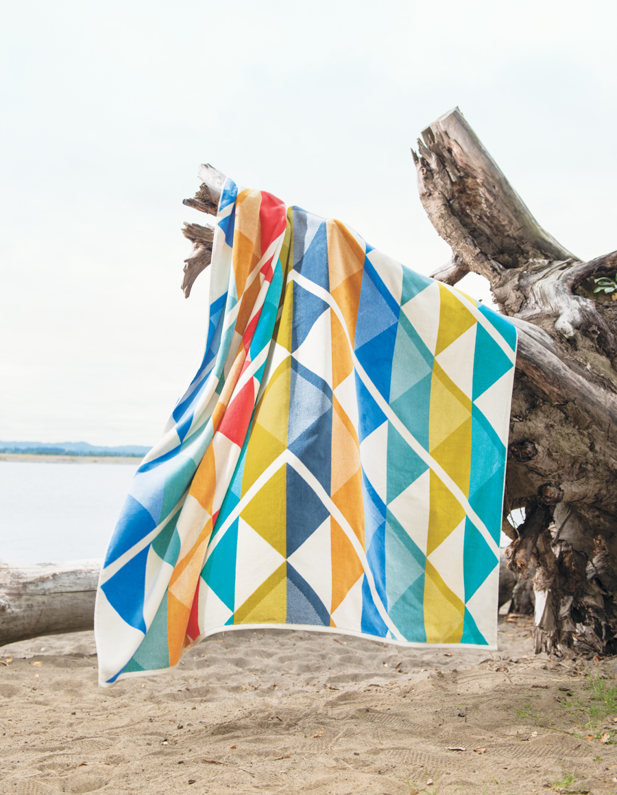 The Serrado towel-for-two hangs on a stump at the beach.
