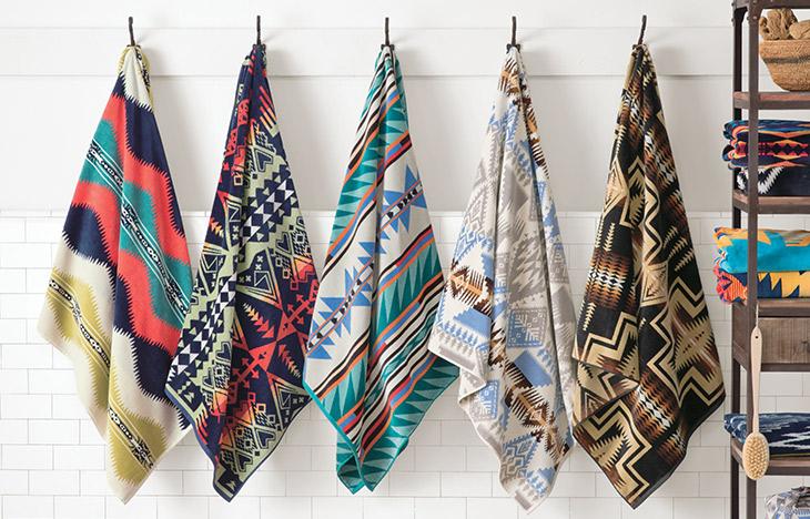FIve Pendleton Towels hanging on a peg rack.