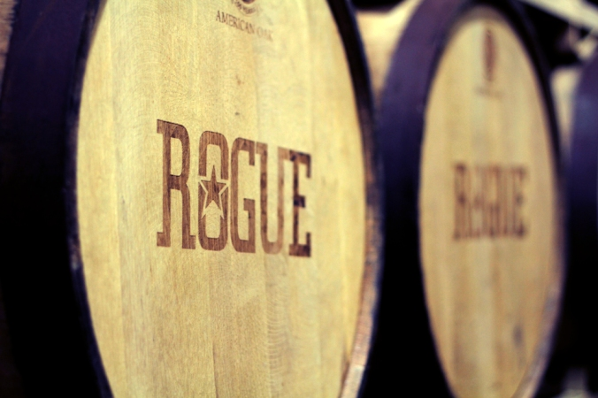 "Wooden aging barrels with ""Rogue"" on them."