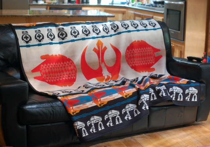 The last Jedi blanket on a black leather couch.
