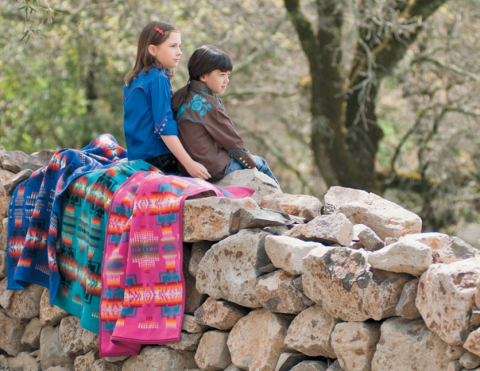 Two girls sit on blankets atop a rock wall.