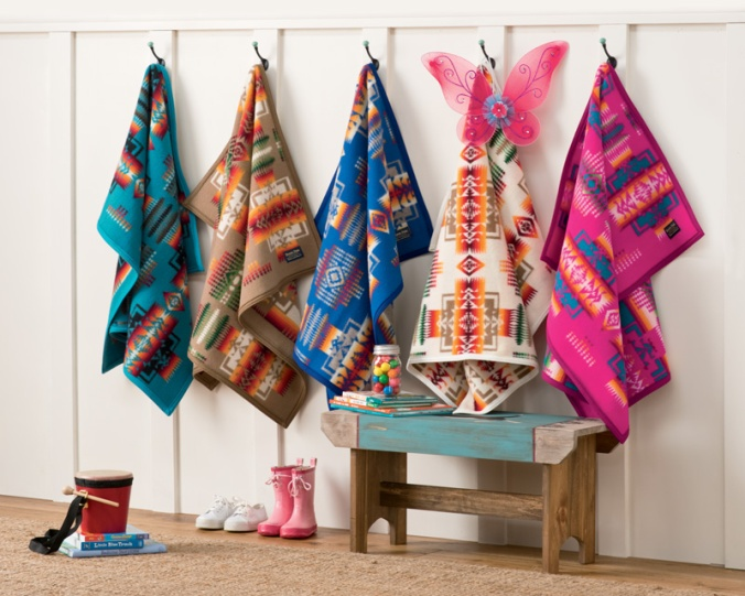 Five Pendleton child-sized blankets hang on pegs.