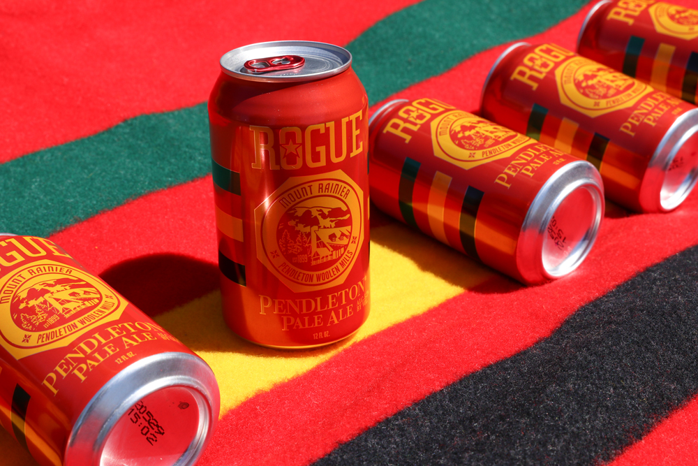 Five cans of Rogue IPA on a Rainier National Park blanket.