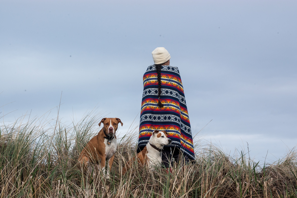 A woman shows off the We Walk Together blanket at Fort Stevens beach, along with two dogs.