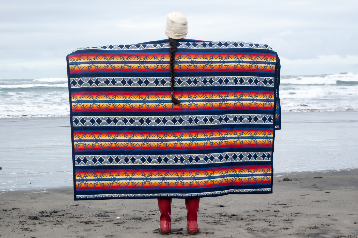 A woman shows off the We Walk Together blanket at Fort Stevens beach.