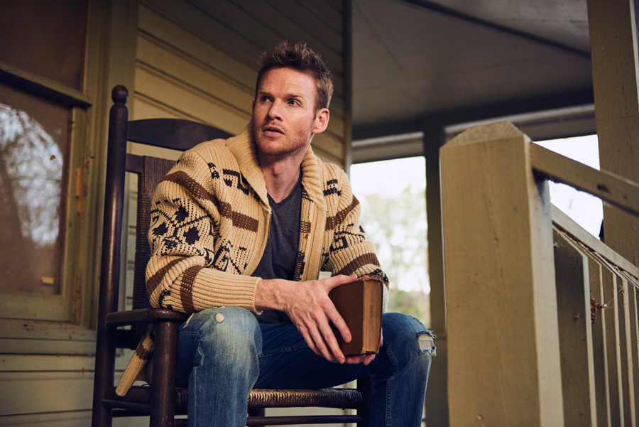 A man sits in a rocking chair on the porch of an oder home, holding a book and wearing a Pendleton Westerley cardigan sweater.