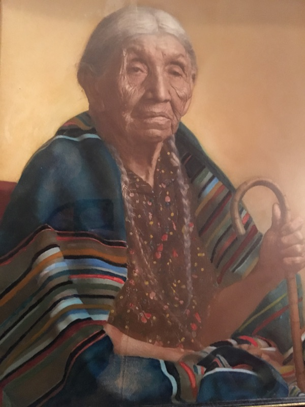 A painting of a Native American matriarch wearing a striped Pendleton blanket. Artist unknown.