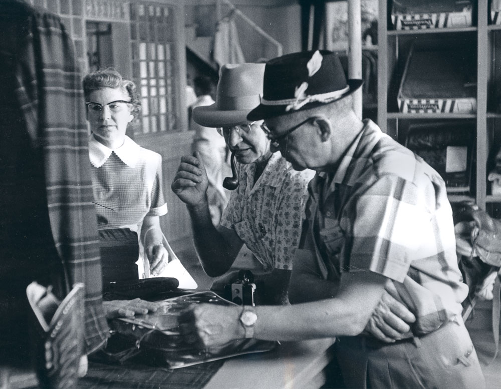 A photo from the Pendleton archives of the Pendleton store in Disneyland: A woman and two gentlemen shopping.