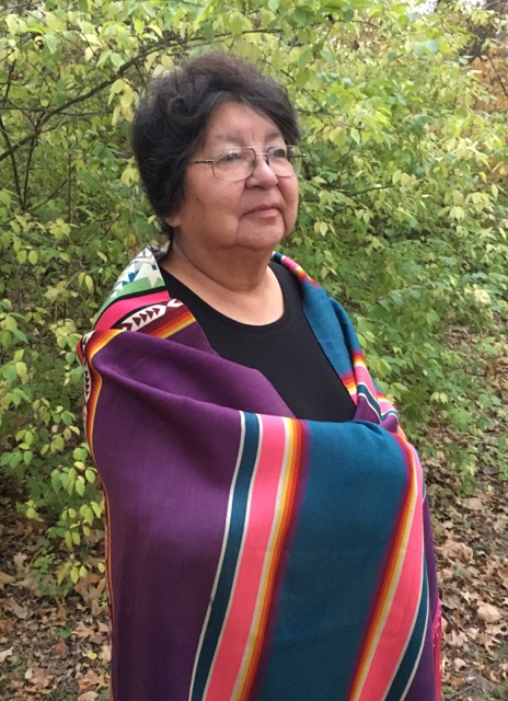 A Native American woman stands in the woods, wrapped in a striped Pendleton blanket.