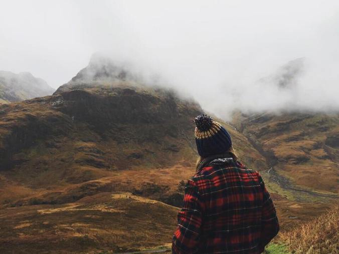 A young woman in a Pendleton coat stands looking at the Three Sisters peaks in Glencoe, Scotland.