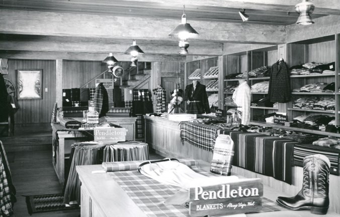 A photo from the Pendleton archives of the Pendleton store in Disneyland: Blanket counter and shirt shelves, with stairway to second floor