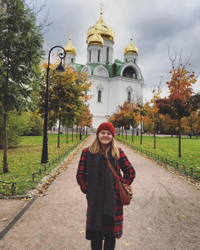 A young woman in a Pendleton coat stands before a church with gold onion domes.