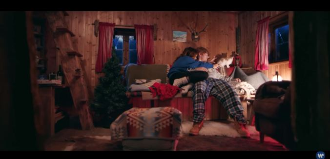 "Screen shot from ""Perfect"" video by Ed Sheeran of a couple on a sofa in a cabin"