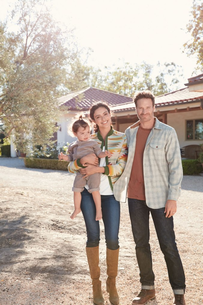A man, woman and child stand in a driveway, she is wearing a Falcon Cove patterned jacket