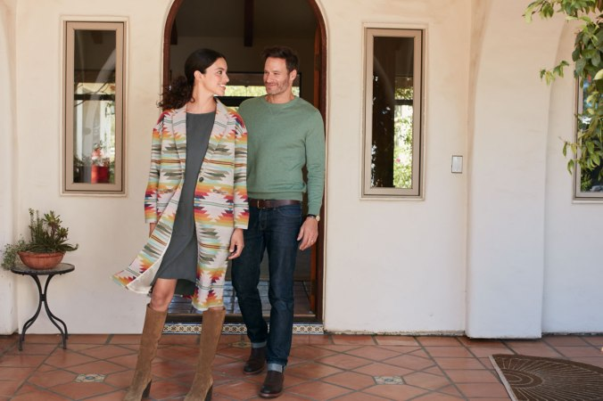 A man and woman stand by a doorway, and she is wearing a coat in the Falcon Cove pattern
