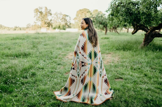 A woman stands by an orchard, wrapped in a Pendleton Falcon Cove blanket