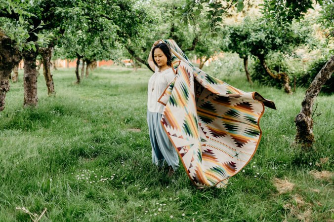 A woman stands in an orchard, swirling the Falcom Cove blanket around her