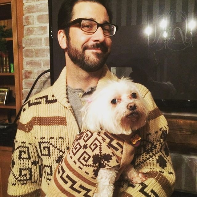 A man holds a white dog, they both are wearing Westerley sweaters