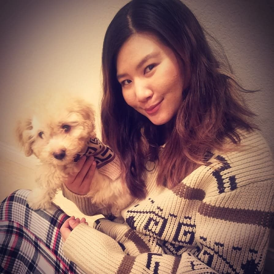 A woman holds a small dog, both are wearing Westerle sweaters