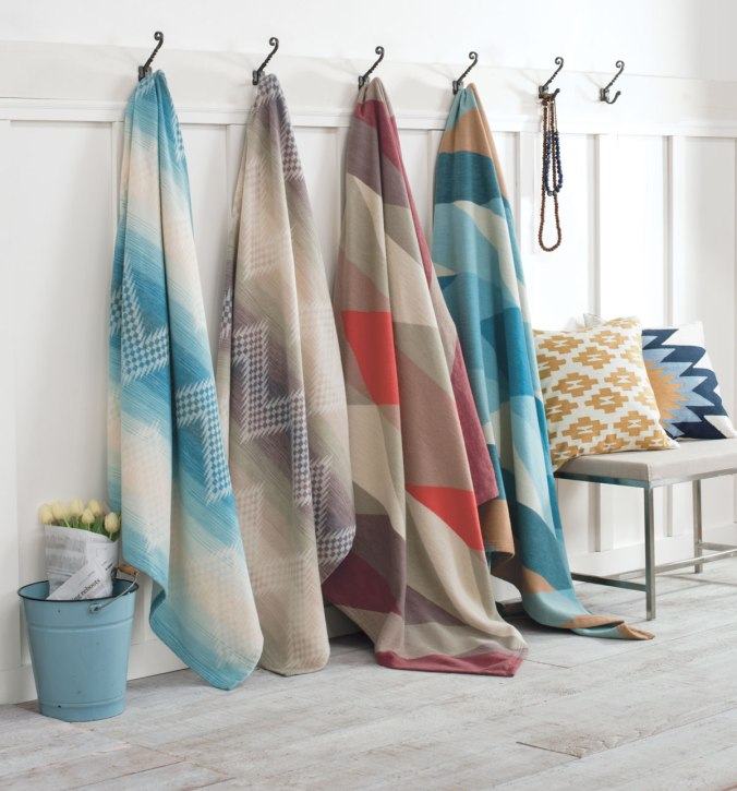 Pendleton cotton bed blankets hanging from hooks against a white wall