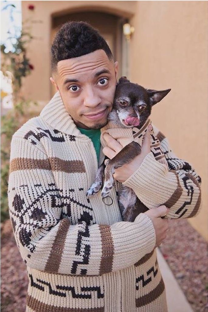 Man holds a small chihuahua, they both are wearing Westerley sweaters