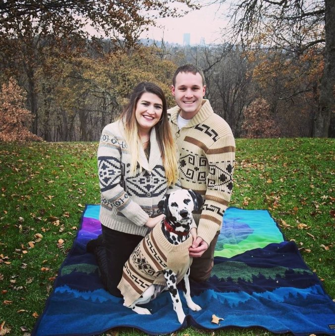 A couple sits on a Pendleton blanket with their Dalmation dog, all wearing Westerley sweaters